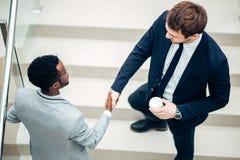 Dwa biznesmenów multiracial handshaking w nowożytnym biurze dla końcówki wielka transakcja zdjęcia royalty free