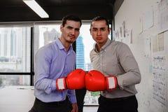Dwa biznesmenów spojrzenia kamera z bokserskimi rękawiczkami w biurze Zdjęcia Royalty Free