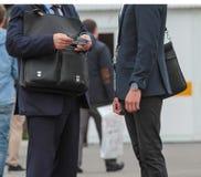 Dwa biznesmen opowiada na ulicie z teczką, zamyka up obrazy stock