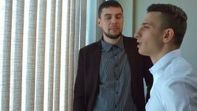 Dwa biznesmen opowiada okno zdjęcie wideo