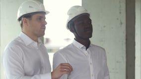 Dwa biznesmen patrzeje daleko od dla nowego projekta podczas gdy pracujący przy budowy miejscem w miasto głąbiku zdjęcie wideo
