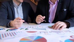 Dwa biznesmena dyskutuje grafika przy biurem zdjęcie wideo