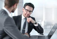 Dwa biznesmena dyskutuje informację od laptopu zdjęcia royalty free