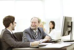 Dwa biznesmena dyskutuje pracę wydają obsiadanie przy ich biurkiem zdjęcia stock