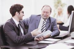 Dwa biznesmena dyskutuje pracę wydają obsiadanie przy ich biurkiem obrazy stock