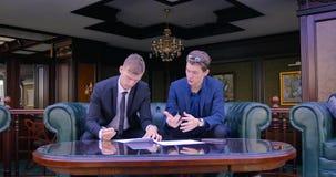 Dwa biznesmena siedzą w pięknych mieszkaniach w kostiumach i dyskutują podpisywanie kontrakt terminy zbiory wideo