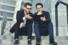 Dwa biznesmena siedzi na schodkach i patrzeje papiery fotografia royalty free