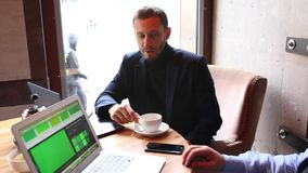 Dwa biznesmena siedzi przy kawiarnia stołem, używać laptop, pijący herbaty i opowiadać zbiory wideo