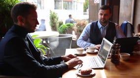 Dwa biznesmena siedzi przy kawiarnia stołem, używać laptop, pijący herbaty i opowiadać zbiory