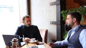 Dwa biznesmena siedzi przy kawiarnia stołem, używać laptop, pijący herbaty i opowiadać zdjęcie wideo