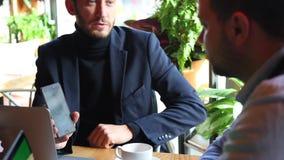 Dwa biznesmena siedzi przy kawiarnia stołem, używać laptop, pijący herbaty i opowiadać Jeden pokazuje inna niektóre ważna informa zdjęcie wideo