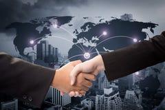 Dwa biznesmena trząść ręki na tło mapie zdjęcia stock