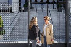 Dwa biznesowej kobiety dyskutują niektóre rzeczy przy wejściem budynek biurowy zdjęcie stock