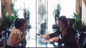 Dwa biznesowej kobiety dyskutuje biznesowego projekt podczas gdy siedzący przy stołem w biurowym naprzeciw each inny używa a zdjęcie wideo