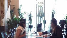Dwa biznesowej kobiety dyskutuje biznesowego projekt podczas gdy siedzący przy stołem w biurze przez od each inny używa a zbiory