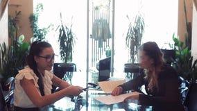 Dwa biznesowej kobiety dyskutuje biznesowego projekta obsiadanie przy stołem w pięknym biurze przez od each inny używa a zbiory