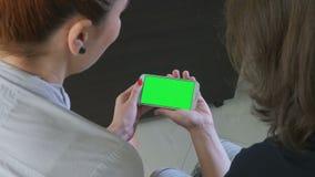 Dwa biznesowej kobiety trzyma smartphone z zieleń ekranem zbiory wideo
