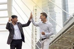 Dwa biznesowych mężczyzna rozochocony klaskać each i ono uśmiecha się inne ręki Obrazy Stock