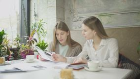 Dwa bizneswomanu dyskutuje prac spojrzenia i zagadnienia przez dokument?w w kawiarni zbiory