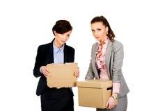 Dwa bizneswomanu przewożenia smutny pudełko Fotografia Royalty Free