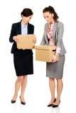 Dwa bizneswomanu przewożenia smutny pudełko Obrazy Stock