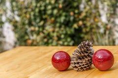 Dwa Bożenarodzeniowej piłki obok sosny konusują na drewnianym stole Zdjęcie Stock