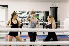 Dwa bokser stoi mi?dzy one kobiety witaj? each inny przed walk?, ich m?ody przystojny trener Bokserscy ludzie fotografia royalty free