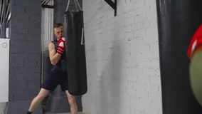 Dwa boksera uderzenia uderza pięścią torby trenuje w gym, sporta pojęcie zbiory wideo
