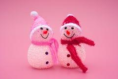 Dwa bożych narodzeń uśmiechnięty zabawkarski bałwan na menchiach Obrazy Royalty Free