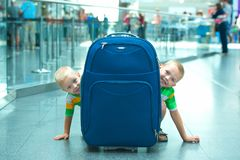 Dwa brata bawić się, chujący za wielką walizką Czas wolny przy lotniskiem czekać na lot fotografia royalty free