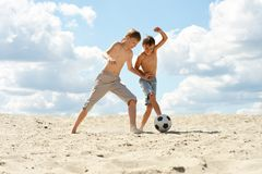 Dwa brata bawi? si? futbol przeciw niebu zdjęcie stock