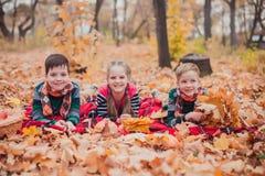 Dwa brata i jeden siostra kłaść w jesień liściach, fotografia stock