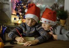 Dwa brata w czerwonych Bożenarodzeniowych kapeluszach piszą liście Święty Mikołaj zdjęcie stock