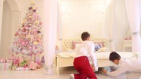 Dwa brata w pośpiechu stawiają przygotowanych prezenty dla rodziców pod drzewem w pięknej sypialni w dniu zdjęcie wideo