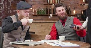 Dwa brodatego mężczyzny po biznesowego spotkania używa NFC płacić contactless zbiory