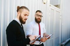 Dwa brodaty biznesmen patrzeje coś zdjęcie stock