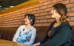 Dwa brunetki młodej kobiety siedzi w cukiernianym mieć rozmowę Zdjęcie Stock