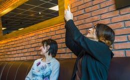 Dwa brunetki młodej kobiety siedzi w kawiarni wpólnie zdjęcie stock
