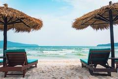 Dwa bryczka holu i s?omianego parasol na tropikalnej pla?y Wybrze?e wyspy Koh Rong Samloem Bezp?atna pusta kopii przestrze? dla t fotografia royalty free