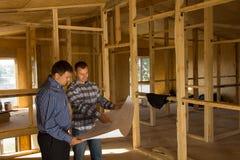 Dwa budowniczego dyskutuje wnętrze dom Zdjęcia Stock