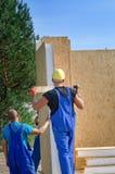 Dwa budowniczego instaluje drewnianego ściennego panelu Obrazy Royalty Free
