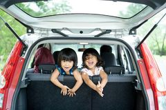 Dwa córka bawić się w samochodowym spojrzeniu i tylnym siedzeniu z powrotem od bagażu obrazy stock