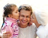 dwa córki całują ich matki Fotografia Royalty Free