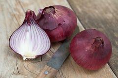 Dwa cały i przyrodnie czerwone cebule na tnącej desce z kuchennym nożem Fotografia Stock
