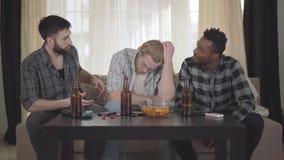 Dwa caucasian i jeden amerykanin afrykańskiego pochodzenia mężczyzny siedzi na kanapie Jeden facet problem, dwa inny koi on w  zbiory wideo