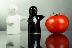 Dwa ceramicznej postaci wskazują pomidoru Fotografia Stock