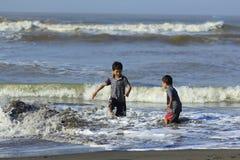 Dwa chłopiec bawić się fale do ich odziewają moczyli fotografia stock
