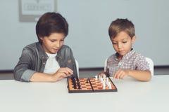 Dwa chłopiec bawić się szachowego obsiadanie przy stołem i zanudzają obraz stock