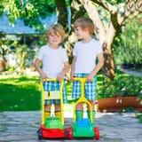 Dwa chłopiec bawić się z gazonu kosiarza zabawkami Obrazy Stock