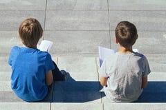 Dwa chłopiec czytelniczej książki siedzi na schodkach outdoors Obraz Stock